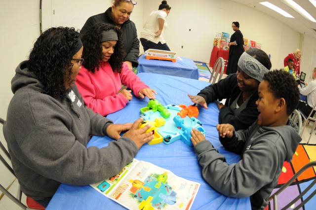 Family members enjoy a game of Hungry Hungry Hippos during Single Parent Family Game Night at the post exchange Dec. 8.