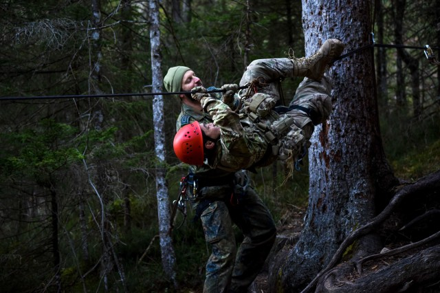 A German soldier instructs a U.S. Army Soldier assigned to the Scout Platoon, 2nd Battalion, 503rd Infantry Regiment, 173rd Airborne Brigade, before rope climbs a ravine during German Mountain Warfare Training in Seinsbach Gorge, Mittenwald, Germany,  Dec. 8th, 2016.  The Mountain Warfare training was conducted from 5 to 16 Dec., to build proficiency in mountain terrain with reconnaissance operations and extreme cold weather survival techniques. This training was alongside other NATO allies including German, Polish, Lithuanian, Latvian and Estonian Armies