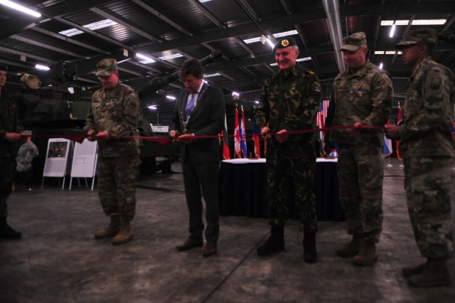 From left, Lt. Gen. Ben Hodges, commanding general, U.S. Army Europe, Edelachtbare Heer J. Som, mayor of Eygelshoven, Netherlands, and Dutch Gen. Tom Middendorp, Chief Defense Staff, Royal Netherlands Army, cut the ribbon to officially open the Army Prepositioned Stock site at Eygelshoven Army Depot-BENELUX, Dec. 15.