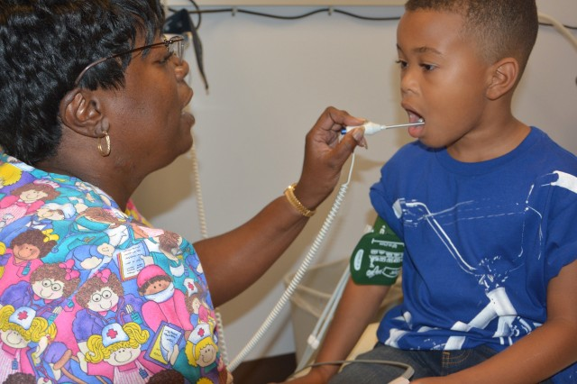 Judenia Wilson, a licensed vocational nurse (LVN) at the Harker Heights Medical Home, takes 6-year-old Nate Williams's temperature. Wilson is one of more than 15 LVNs at the Harker Heights clinic. The hallmark of CRDAMC's clinics is patient-centered care, which promotes a long-term relationship between provider and patient. The patient's medical team, which includes physicians, nurses and behavior health specialists, coordinate their care and develop individualized healthcare plans for them as they transition through life.