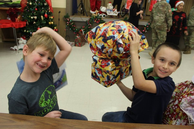 Two first-graders discuss what their presents could be as they try to contain their excitement.
