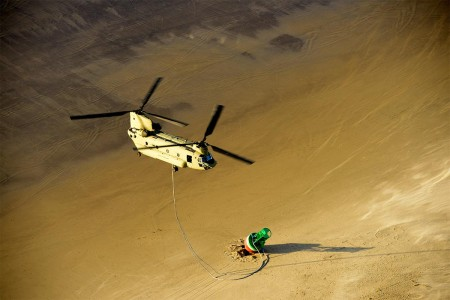 An aircrew aboard a U.S. Army CH-47 Chinook helicopter, from Joint Base Lewis-McChord, Wash., prepares to take the load of a 14,000 pound buoy that washed ashore just south of the entrance to Tillamook Bay, in Garibaldi, Ore., Dec. 12, 2016. The Army aircrew assisted the Coast Guard in recovering the beached buoy that normally marks the navigable channel into Tillamook Bay.