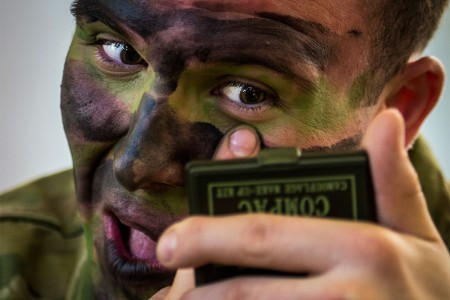 "1st Lt. Oliver Salman puts on camouflage paint, Feb. 6, 2016, before a night static-line jump during ""large package week"" training operations on Pope Army Airfield, N.C. The training helps prepare airmen and soldiers for a subsequent joint access exercise."