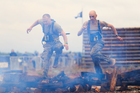 Staff Sgt. Erich Friedlein and Capt. Robert Killian, jump over smoldering logs during the Spartan Race that kicked off Day 2 of the grueling 33rd annual Best Ranger Competition at Fort Benning, Ga., April 16, 2016. The competition is a three-day event consisting physical, mental, and technical challenges in honor of Lt. Gen. David E. Grange Jr.