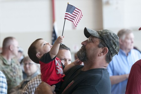 Sgt. Rowdy Blackmon's son waves an American flag in the arms of his grandfather, father to Blackmon at the Army Aviation Support Facility in Lexington, Ok., June 5, 2016. Members of 1st Airfield Operations Battalion, 245th Aviation Regiment gather with family and friends before deploying to the Middle East to provide air traffic control operations for military and civilian aircraft.