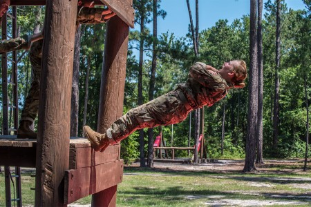 A Soldier in Basic Combat Training with Company A, 3rd Battalion, 13th Infantry Regiment, at Fort Jackson, S.C., exits the Skyscraper obstacle by falling several feet onto a mat at the confidence course, June 22.