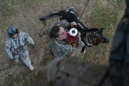 A UH-60L Black Hawk helicopter hoists Spc. Courtney Moreland, a military working dog handler, and her dog, Puma, during K-9 evacuation training at Soto Cano Air Base, Honduras. Moreland is assigned to Joint Task Force-Bravo's Joint Security Forces.