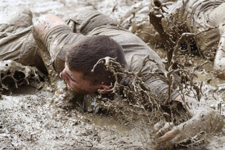 A poolee with the Arkansas Army National Guard Recruit Sustainment Program dives headfirst into a mud pit, March 13, 2016, at an obstacle course event during the Recruit Warrior Challenge at Fort Chaffee Joint Maneuver Training Center, Ark. Recruits competed against each other to measure physical strength and give them an idea of how Army Basic Combat Training will be.