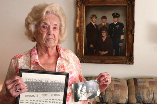 Willie McLaney holds a photo of the Airborne Test Platoon, left; and a photo of her husband, Lester McLaney, during World War II. Behind her is a family portrait taken before her husband's death in 1972. Lester McLaney was a member of the Test Platoon and went on to make four combat jumps during World War II , and participated in several campaigns in Northern Africa and Europe.