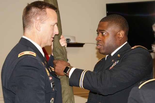 (Left) Col. Bradly Boganowski, commander of the 800th Logistics Support Brigade, receives the cased battalion colors from Maj. Marquis Wilson, commander of the 4th Battalion, 321st Regiment, at the battalion's deactivation ceremony at Redstone Arsenal, Ala., Dec. 18, 2016. The deactivation is part of the 800th LSB restructuring, which is a result of the overall Army Reserve drawdown.