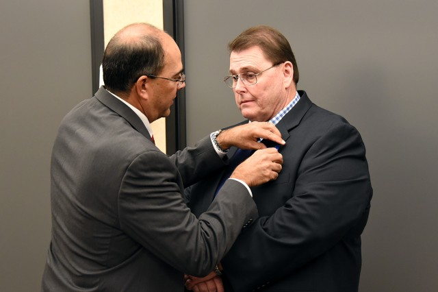 Thomas Webber, acting director, U.S. Army Space and Missile Defense Command/Army Forces Strategic Command Technical Center, pins the Meritorious Civilian Service Award on Doug Burdette, engineer, during his retirement Dec. 16 at the command's Redstone Arsenal, Alabama headquarters. Burdette retired with 30 years of federal service.