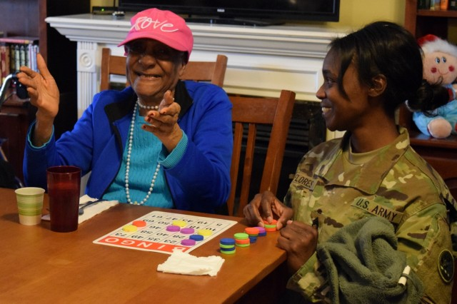 Georgia Army National Guard Sgt. 1st Class Maurika Flores brings joy to a resident of Azalea Manor Assisted Living Facility. The Guardsmen visited with residents, presented gifts, played Bingo and chatted with residents.
