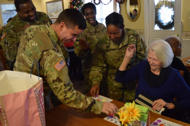 Georgia Guardsmen laugh with residents of the Azalea Manor Assisted Living Facility during a holiday visit. Twenty Georgia Guardsmen visited the residents and provided gifts and holiday cheer.