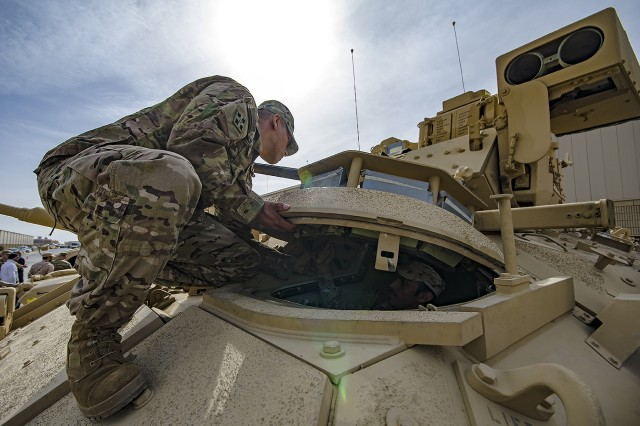 Sgt. 1st Class Christopher Trejo, contracting officer representative, 401st Army Field Support Battalion-Kuwait shows a Kuwait Army noncommissioned officer how to operate the driver's hatch of a Bradley Fighting Vehicle during a tour of Army Prepositioned Stocks-5 at Camp Arifjan, Kuwait, Dec. 19. (U.S. Army Photo by Justin Graff, 401st AFSB Public Affairs)