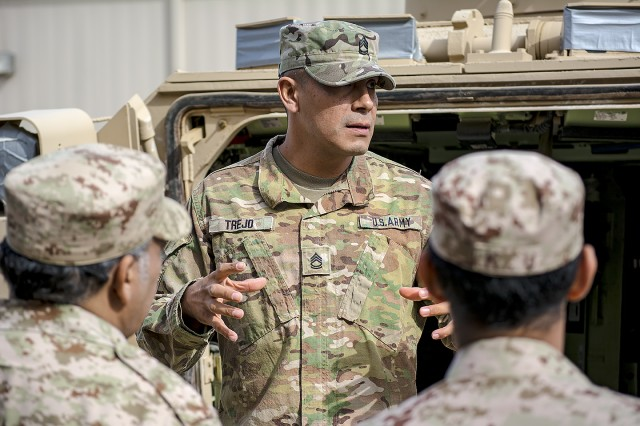 Sgt. 1st Class Christopher Trejo, contracting officer representative, 401st Army Field Support Battalion-Kuwait speaks to a group of Kuwait Army logistics officers and noncommissioned officers about vehicle maintenance during a tour of Army Prepositioned Stocks-5 at Camp Arifjan, Kuwait, Dec. 19. (U.S. Army Photo by Justin Graff, 401st AFSB Public Affairs)