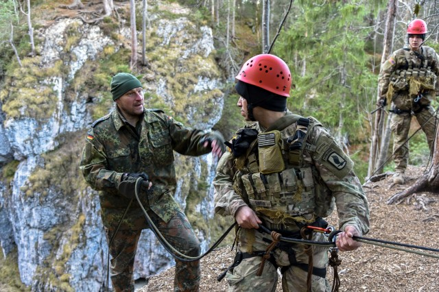 A German soldier instructs a U.S. Army Soldier assigned to the Scout Platoon, 2nd Battalion, 503rd Infantry Regiment, 173rd Airborne Brigade, before repelling down a ravine during German Mountain Warfare Training in Seinsbach Gorge, Mittenwald, Germany, Dec. 8, 2016. The Mountain Warfare training was conducted from 5 to 16 Dec., to build proficiency in mountain terrain with reconnaissance operations and extreme cold weather survival techniques. This training was alongside other NATO allies including German, Polish, Lithuanian, Latvian and Estonian armies.