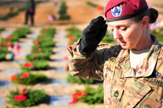 Sgt. 1st. Class Jean Mott, a XVIII Airborne Corps Soldier, salutes a fallen Soldier's grave during a Wreaths Across America event at the Sand Hills State Veteran's Cemetery in Spring Lake, N.C. Dec. 17, 2016. Wreaths Across America, an annual-event that began in Maine in 1992, is conducted as a way to honor fallen service members.