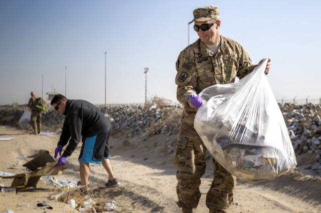 Volunteers pick up trash during an organized cleanup, Operation Flying Debris, on Dec. 16 at Camp Arifjan, Kuwait. The cleanup, hosted by Area Support Group - Kuwait, included service members and civilians who collected over 50 bags of trash and recyclable material.