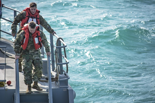 Soldiers from the 401st Army Field Support Battalion-Kuwait descends stairs to the load deck in anticipation of rougher seas aboard the Army Landing Craft Utility 2016 Corinth during a sea trial at Kuwait Naval Base, Kuwait, Dec. 21. (U.S. Army Photo by Justin Graff, 401st AFSB Public Affairs)