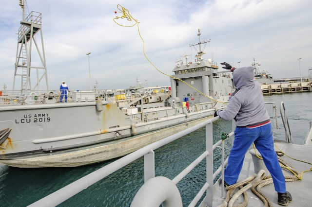 A crew member tosses a rope from the Army Landing Craft Utility 2016 Corinth to an adjacent vessel while returning port during a sea trial at Kuwait Naval Base, Kuwait, Dec. 21. (U.S. Army Photo by Justin Graff, 401st AFSB Public Affairs)