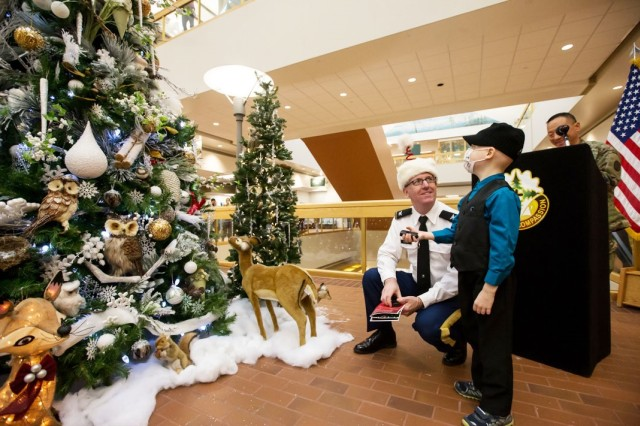 Garen Moore, 6, and Col. John Kent, Madigan's deputy commanding officer, light Madigan's Christmas Tree on Dec. 2 in the Medical Mall.