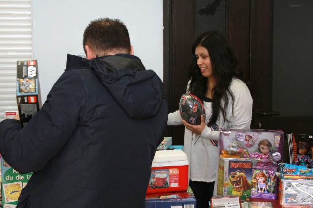 Marine Corps Sgt. Mayra Lopez from the Landstuhl Regional Medical Center Marine Liaison Detachment helps a father choose gifts for his children Dec. 14 at the German Red Cross in Landstuhl, Germany. Lopez' unit, along with help from Army and Air Force units, collected more than 880 toys during the annual Toys for Tots drive to give to local German, American and refugee families.