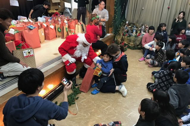 Sgt. 1st Class Hector Valadez and Sgt. Perique Roseberry dress up as Santa Claus and Santa's helper to deliver gifts for the holidays to the children of the Holy Family Home orphanage in Osaka, Japan