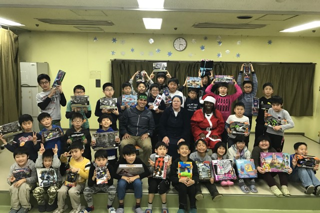 Sgt. 1st Class Hector Valadez (middle, left) and Sgt. Perique Roseberry (middle, right) pose with children and staff of Holy Family Home orphanage in Osaka, Japan after opening gifts.