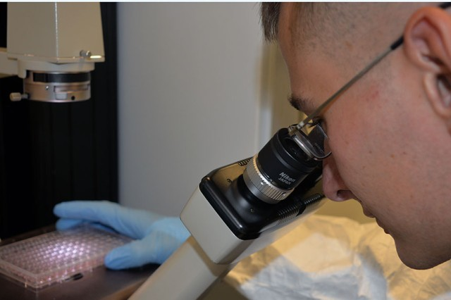 Sgt. Christopher A. Springer examines cell growth at the Walter Reed Army Institute of Research in Silver Spring, Maryland. Springer, a lab technician, was among the first military personnel in the United States who took part in the Army's efforts to control the spread of Zika.