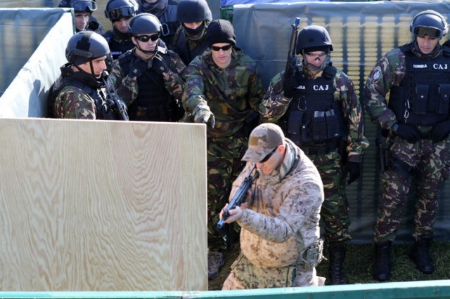 BELGRADE, Serbia- A U.S. Navy SEAL assigned to Naval Special Warfare Unit 2 demonstrates proper procedures of clearing an area of engagement during a close quarter combat scenario during a Special Operations Command Europe Joint Combined Exchange Training Nov 28. Close quarter combat drills are conducted to give the operators the ability to make split-second decisions and to become proficient with their weapons. (photo by Staff Sgt. Larraine Whetstone/24th Press Camp HQ)