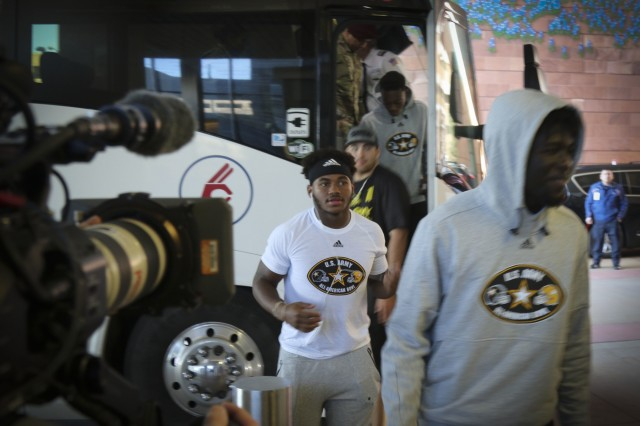 A group of High-school athletes from the U.S. Army All-American Bowl east and west teams step off a bus in front of the University Hospital in San Antonio before visiting sick and injured children as part of a community relations event.