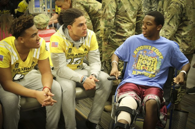 Hunter Echols (Left), a high-school student and defensive end from Los Angeles, California and Jaelan Phillips (center), also a high-school student and defensive end from Redlands, California, who will both play in the Army All-American Bowl on Jan. 7, visit with 15-year-old Jalen Williams, one of the children in the Children's Health Department of the University Hospital in San Antonio.