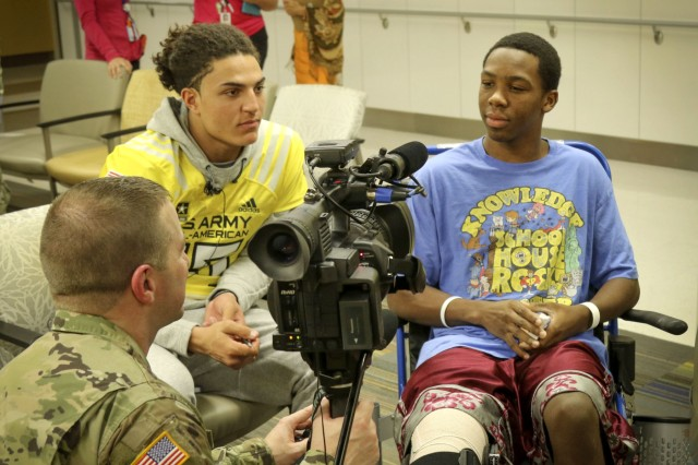 Army Reserve Staff Sgt. Steve Engle, a broadcast journalist with the 367th Mobile Public Affairs Detachment, 318th Press Camp Headquarters, interviews 15-year-old Jalen Williams (right), one of the children in the Children's Health Department of the University Hospital in San Antonio Jan. 3, as Jaelan Phillips (left) a high-school student and defensive end for the west team of the Army All-American Bowl looks on.