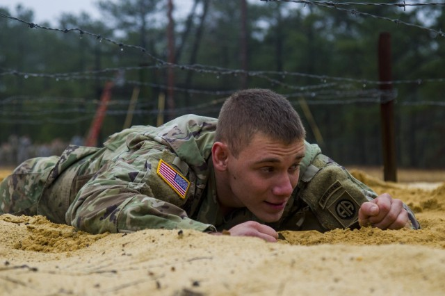 "Pvt. Adam Klover, a rigger assigned to the 151st Division Aerial Delivery Company, 189th Combat Sustainment Support Battalion ""Superchargers,"" moves through the damp sand for the low crawl obstacle as he tackles the air assault school obstacle course on Fort Bragg, N.C., January 4, 2017.  Air Assault teaches Paratroopers and Soldiers how to use rotary wing assets to accomplish the mission.  (U.S. Army photo by Sgt. Daniel Schroeder, 82nd Airborne Division Sustainment Brigade, Released)"