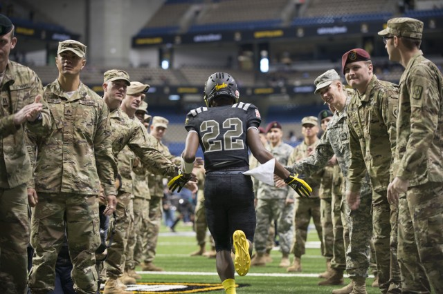 A East player runs past a tunnel of Soldier mentors before the Army All-American Bowl in San Antonio Jan. 7, 2017.  The East team beat the West team 27-17 in the annual game.