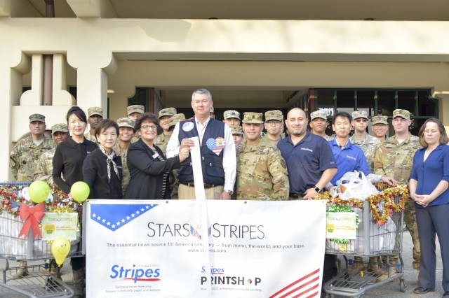 John R. Hahn, Ms. Solange Gates, Command Sgt. Maj. Juan A. Abreu and HHC Soldiers gather in front of the Camp Walker Commissary to celebrate the DeCA $1,000 Shopping Spree on November 18.