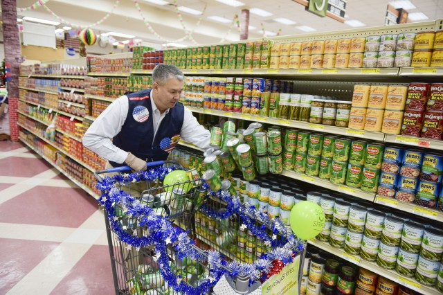John R. Hahn sweeps canned goods into his cart during the DeCA $1,000 Shopping Spree on November 18.