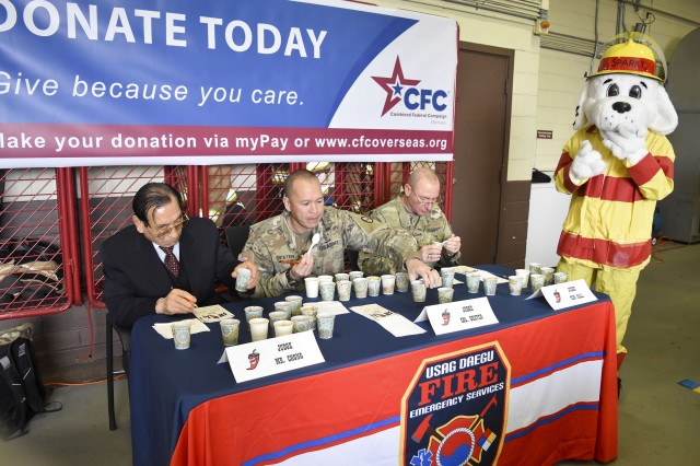 Mr. Chong, Yong Sok, Col. Dexter, Command Sgt. Maj. Hall judge the 12 chilies competing in the Combined Federal Campaign's Chili Cook-Off Fundraiser