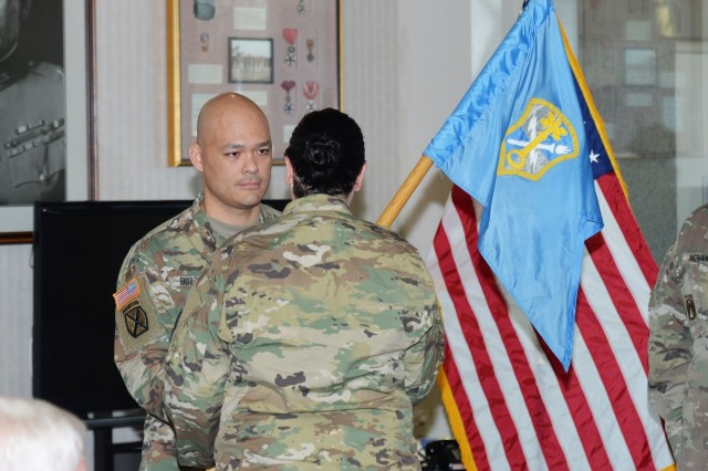 Capt. Michael E. Buzzell, incoming commander, Headquarters and Headquarters Company, U.S. Army Intelligence and Security Command (rear), accepts the command guidon from Col. Nichoel E. Brooks, INSCOM deputy commander, during the INSCOM HHC change of command ceremony at Fort Belvoir, Virginia, Dec. 14.  Buzzell officially assumed command of the company supporting INSCOM's operations from Capt. Geoff M. Terman.  (U.S. Army photo by Sgt. Jeff Storrier)