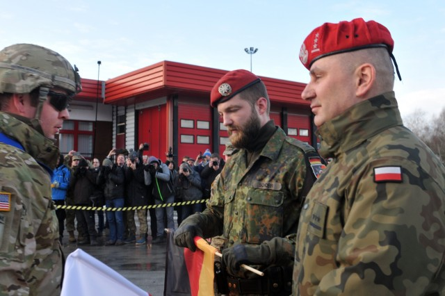 Capt. Bill Whelan, Commander of 1st Battalion, 8th Infantry, 3rd Armored Brigade Combat Team, 4th Infantry Division gives a German Soldier a German flag to show the significance of crossing over to the Polish border after conducting a three-day convoy, Jan. 12, for their nine-month deployment training alongside multinational partners. 3-4 ABCT's arrival marks the start of back-to-back rotations of armored brigades in Europe as part of Atlantic Resolve. This rotation will enhance deterrence capabilities in the region, improve the U.S. ability to respond to potential crises and defend allies and partners in the European community. U.S. forces will focus on strengthening capabilities and sustaining readiness through bilateral and multinational training and exercises. (Photo by Staff Sgt. Elizabeth Tarr)