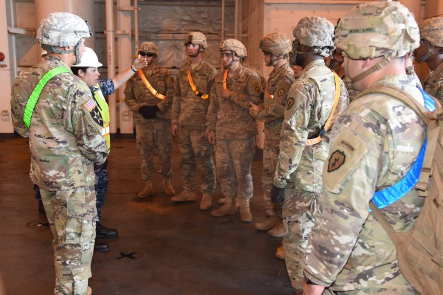 Lt. Cmdr. Cindy Suarez, Fleet Logistics Center, Ocean Terminal Director conducts a safety briefing and provides instructions to Warrior Brigade Soldiers on on-load procedures.