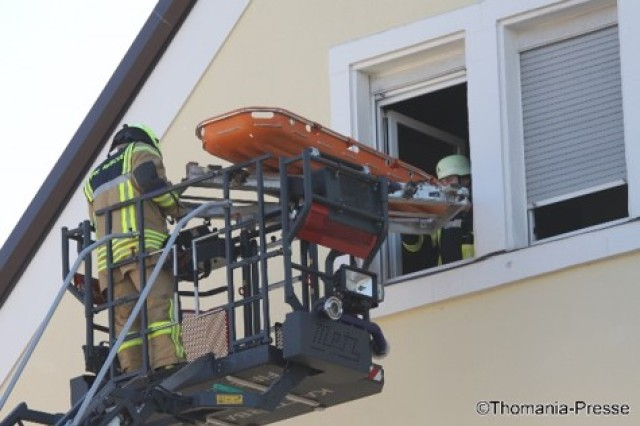 A U.S. Army firefighter from the Katterbach Fire Department is at the top of the aerial ladder, is waiting to move a local Ansbach citizen, who is in serious condition, from a four-story apartment building.