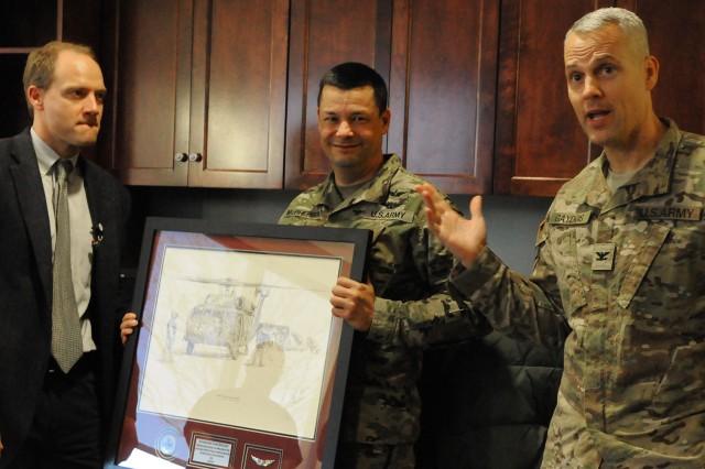 Col. Steven Gaydos, USASAM Occupational Medicine program director (right), and Col. Mark McPherson, USASAM dean, present a MedEvac helicopter print to Dr. Jeremiah Maddox of Southern Bone & Joint Specialists in Dothan.
