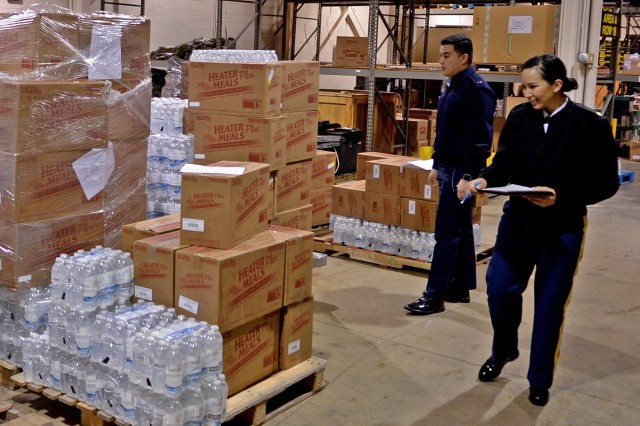 U.S. Army Maj. Beatriz Florez from the 4th Sustainment Command (Expeditionary) out of San Antonio, Texas, reviews items at Joint Base Myer-Henderson Hall, Jan. 10, 2017, that will be used in this year's Presidential Inauguration. Assisting her is U.S. Air Force 2nd Lt. Anthony Garcia Jr.