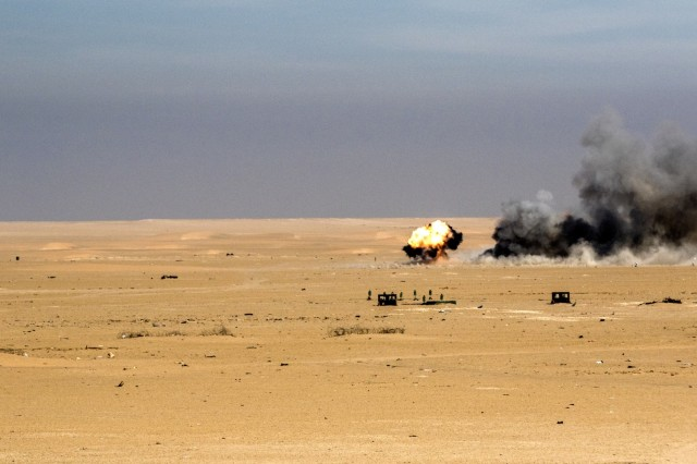 "An M30A1 explodes on target vehicles configured into a convoy at Udairi Training Range in Kuwait, recently. The munitions are being used to replace ""cluster bomb"" munitions with tungsten steel pellets to target soft vehicles and enemy personnel without leaving potential unexploded ordinance on the battlefield."