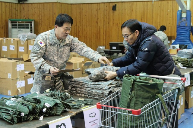 A 32nd Korean Service Corps Company serviceman distributes organizational clothing and individual equipment to a mobile at Station #4 during the mobilization exercise at Daebong Elementary School, Dae