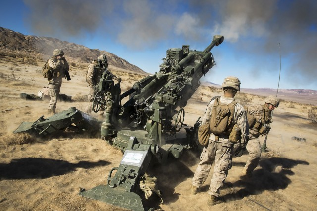 """Marines with Battery K, 3rd Battalion, 11th Marine Regiment, fire an M777A2 Howitzer in the Quackenbush Training Area aboard the Marine Corps Air Ground Combat Center, Twentynine Palms, Calif., Dec. 3, 2016, during the regiment's """"Top Gun"""" competition."""