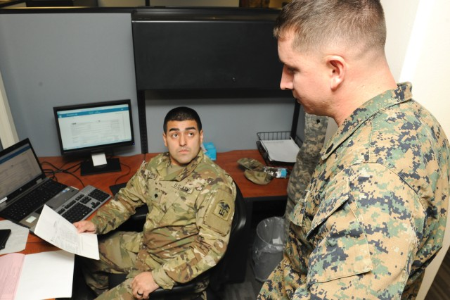Spc. Nate Barbosa, a tax center volunteer, helps Marine Staff Sgt. Josh Owen start his tax return in the Fort Leonard Wood Tax Center Tuesday.