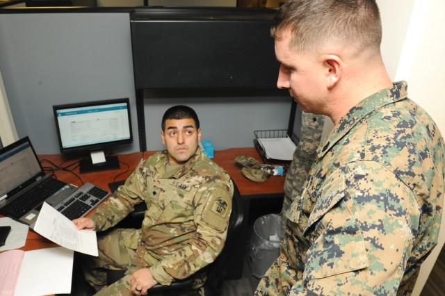 Spc. Nate Barbosa, a tax center volunteer, helps Marine Staff Sgt. Josh Owen start his tax return in the Fort Leonard Wood Tax Center Tuesday.