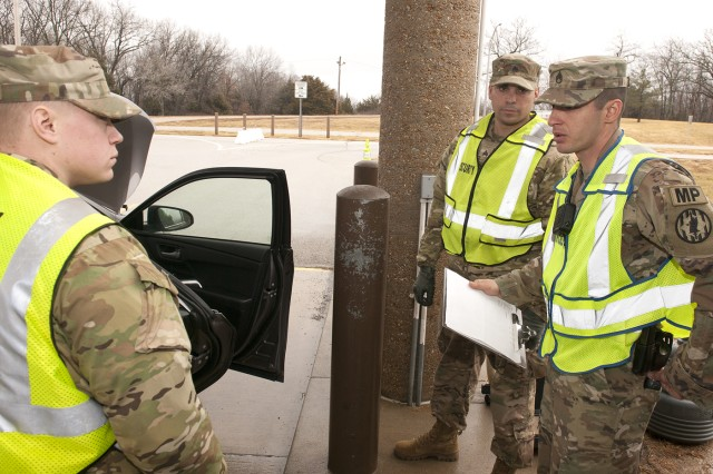 Staff Sgt. Andrew Averett, Physical Security noncommissioned officer in charge, right, provides feedback to 1st Bn., 138th Inf. Reg. Soldiers following a vehicle inspection Monday.